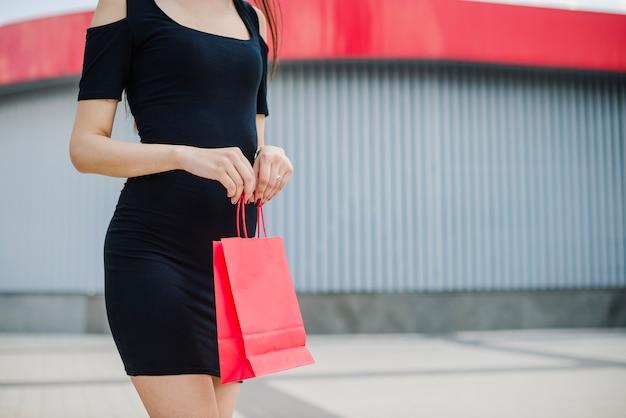 Черное платье с красной сумкой