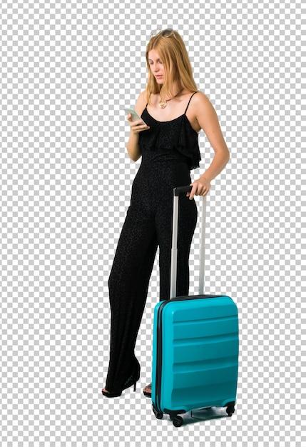 Blond dziewczyna podróżuje z jej walizką wysyła wiadomość lub email z wiszącą ozdobą Premium Psd