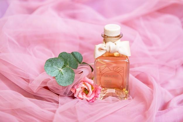 Butelka Perfum Z Kwiatami Na Różowej Powierzchni Tekstylnej Premium Psd
