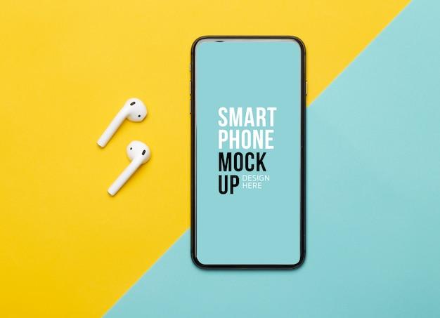Czarny Smartfon Z Ekranem I Bezprzewodowe Słuchawki Na żółtym I Niebieskim Tle. Premium Psd