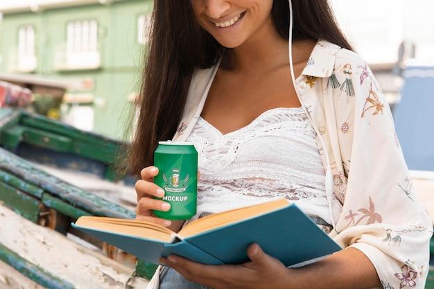 Kobieta Czytająca Książkę I Pijąc Napoje Gazowane Podczas Słuchania Muzyki Darmowe Psd