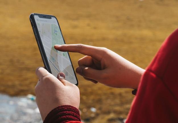 Kobieta na zewnątrz za pomocą aplikacji mapy smartphone Premium Psd