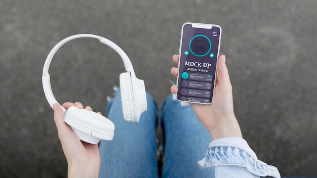 Kobieta Trzyma Telefon Z Makietą Aplikacji Muzycznej I Słuchawkami Premium Psd