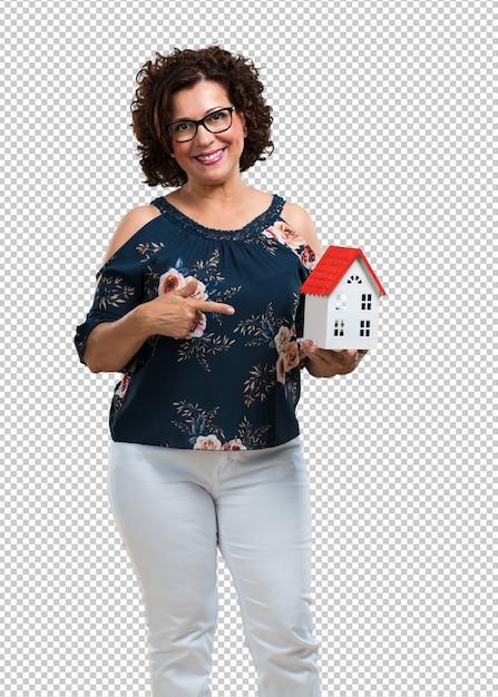 Kobieta W średnim Wieku Szczęśliwa I Pewna Siebie, Pokazująca Miniaturowy Model Domu, Próbująca Go Sprzedać, Dom I Rodzinę Premium Psd