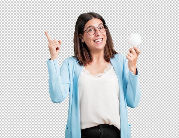 Kobieta w średnim wieku wesoła i podekscytowana, skierowana w górę, trzyma żarówkę jako symbol pomysłu, wyobraźni, płynności i mądrości, inspirujące zdjęcie Premium Psd