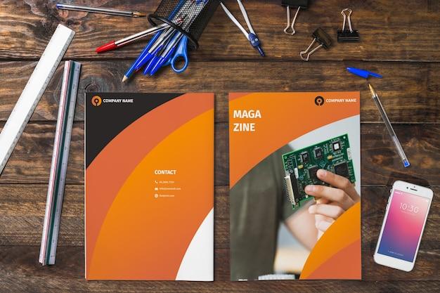Magazine i smartphone makieta na drewnianym stole z długopisy i linijki Darmowe Psd