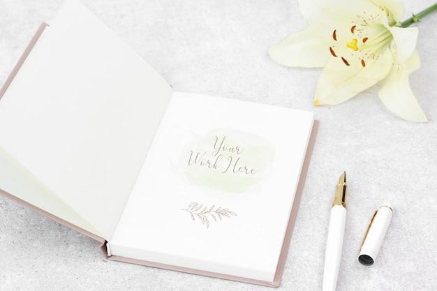 Makieta notatki z lilia i białe pióro Premium Psd