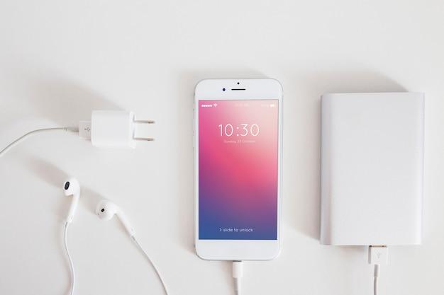 Makieta smartfona z kablem do ładowania i słuchawkami Darmowe Psd