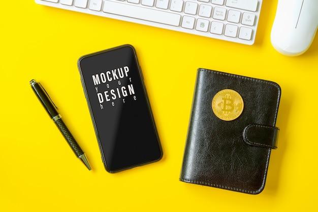 Makieta Telefonu Komórkowego Na żółtym Stole Z Bitcoin Na Notebooku. Premium Psd