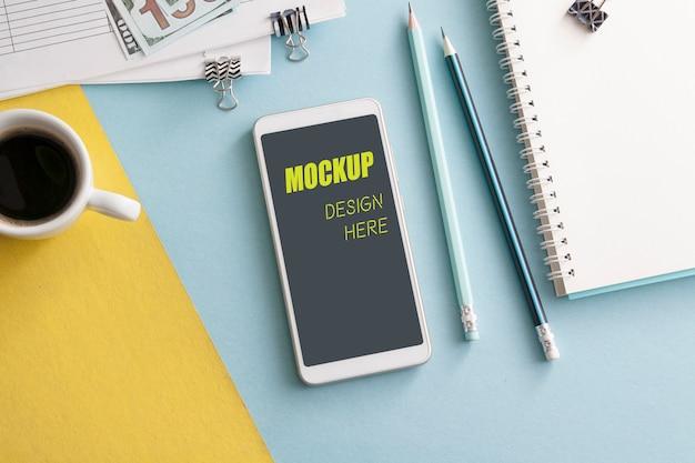 Makiety Smartfona Na Kolorowym Tle Pulpitu Z Notebooka, Ołówków I Kawy Premium Psd