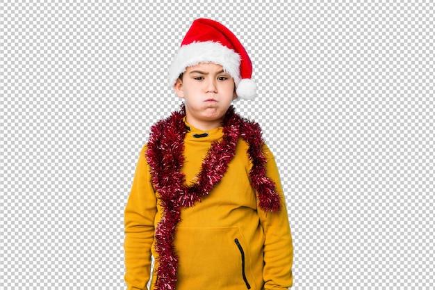 Mały chłopiec obchodzi boże narodzenie w kapeluszu santa wieje policzki, ma zmęczony wyraz. koncepcja wyrazu twarzy. Premium Psd
