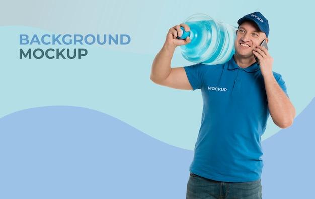 Mężczyzna Dostawy Posiadający Dużą Butelkę Wody Podczas Rozmowy Przez Telefon Darmowe Psd