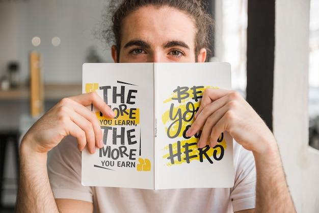 Mężczyzna trzyma makietę okładki książki przed twarzą Darmowe Psd