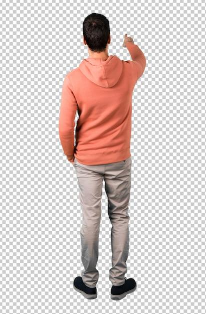 Mężczyzna W Różowej Bluzie Wskazuje Z Powrotem Z Palcem Wskazującym Przedstawiający Produkt Od Tyłu Premium Psd