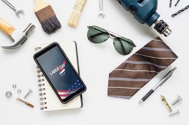 Mieszkanie leżało na makiecie smart phone z okazji święta pracy w usa i podstawowych narzędzi dla pracowników Premium Psd