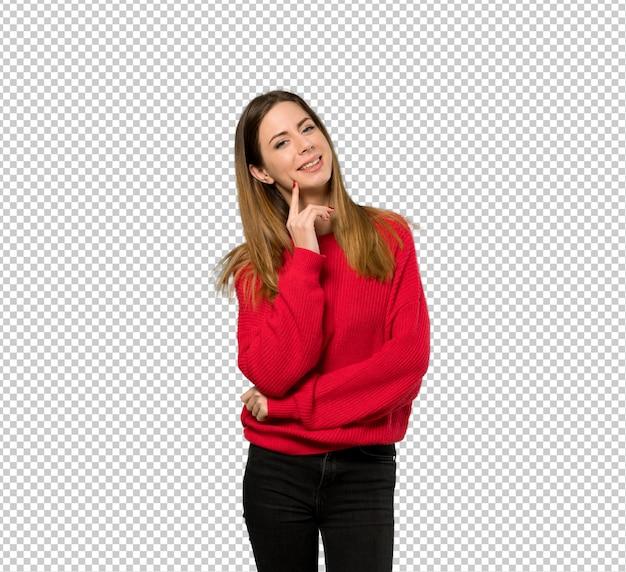 Młoda kobieta myśleć pomysł z czerwonym pulowerem podczas gdy przyglądający up Premium Psd