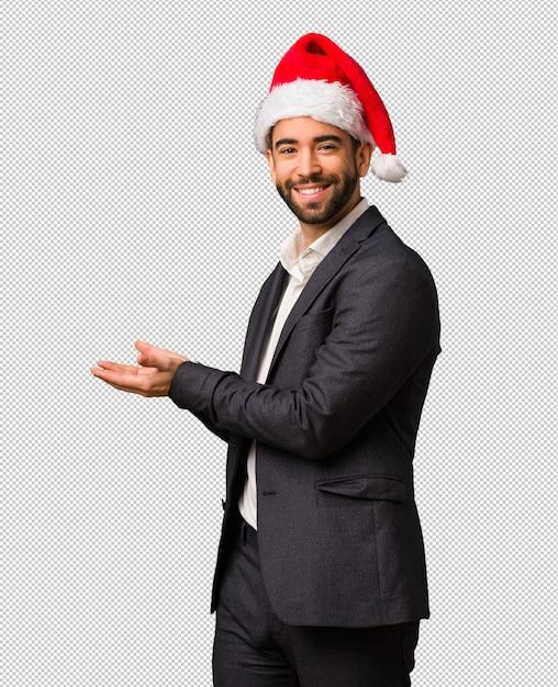 Młody Biznesowy Mężczyzna Jest Ubranym Santa Kapeluszowego Mienia Coś Z Rękami Premium Psd