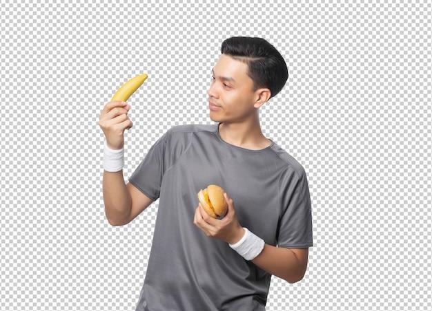 Młody Przystojny Azjatycki Mężczyzna Trzyma Banana I Hamburgera Premium Psd