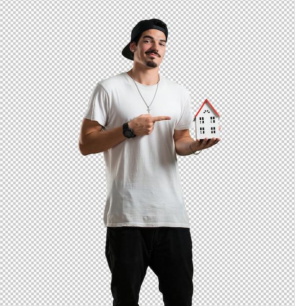 Młody Raper Człowiek Szczęśliwy I Pewny Siebie, Pokazując Miniaturowy Model Domu Premium Psd