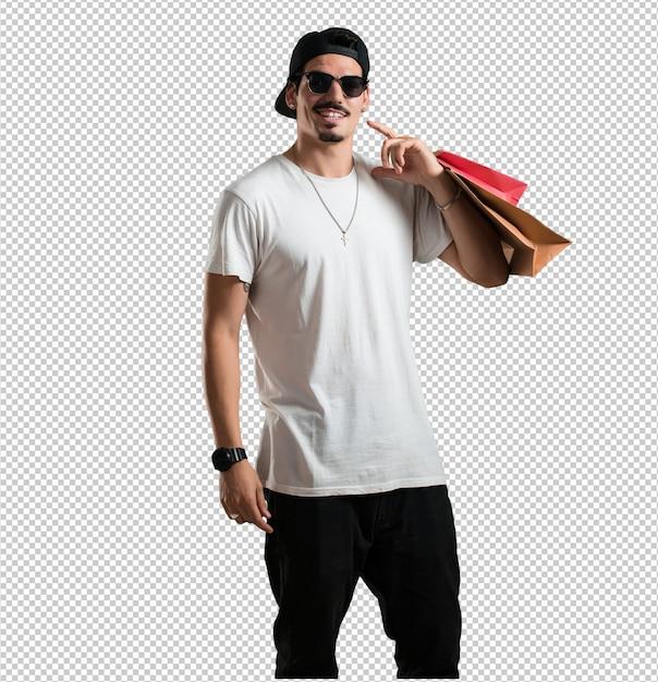 Młody raper, wesoły i uśmiechnięty, bardzo podekscytowany, niosąc torby na zakupy, gotowy na zakupy i poszukiwanie nowych ofert Premium Psd