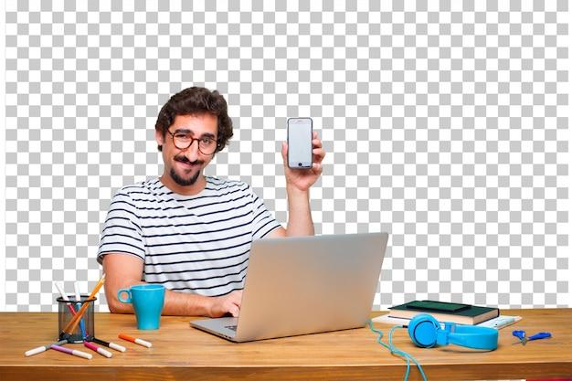 Młody szalony grafik na biurku z laptopem i telefonem z ekranem dotykowym Premium Psd