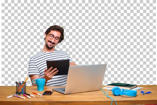 Młody szalony projektant graficzny na biurku z laptopem i tablet z ekranem dotykowym Premium Psd