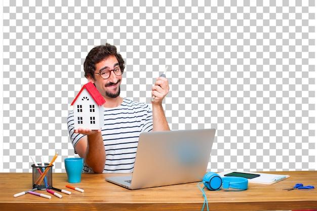 Młody Szalony Projektant Graficzny Na Biurku Z Laptopem Iz Modelem Domu Premium Psd