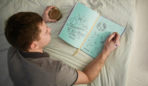 Odgórny Widok Mężczyzna Writing W Notatniku Na łóżku Darmowe Psd