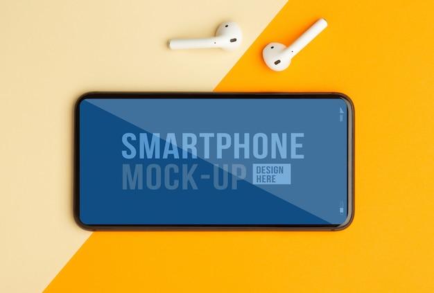 Płaski Układ, Widok Z Góry Pomarańczowego Biurka Na Biurko Z Szablonem Makiety Smartfona Do Projektowania I Bezprzewodowe Słuchawki. Nowoczesna Przestrzeń Do Pracy Premium Psd