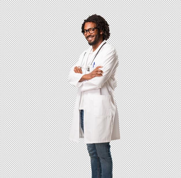 Przystojny amerykanin afrykańskiego pochodzenia lekarz medycyny krzyżuje jego ręki, uśmiechnięty i szczęśliwy Premium Psd