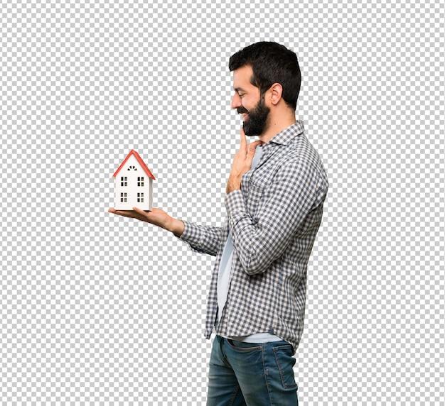 Przystojny mężczyzna trzyma troszkę dom z brodą Premium Psd