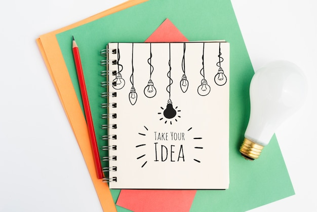 Realistyczna żarówka i notatnik z rysunkami żarówek Darmowe Psd