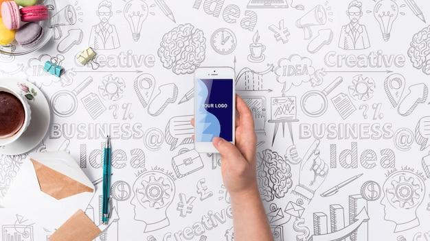 Ręka z mobilnym biurka pojęciem z narzędziami Darmowe Psd