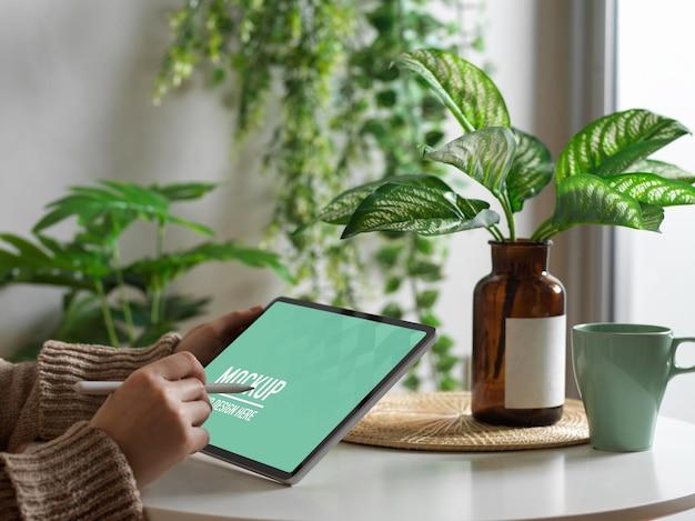 Ręka Za Pomocą Makiety Cyfrowego Tabletu Na Stoliku Do Kawy Premium Psd