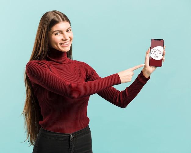 Średni Strzał Szczęśliwa Dziewczyna Wskazuje Na Jej Telefon Darmowe Psd