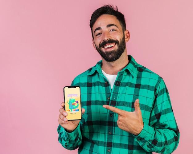 Uśmiechnięty młody człowiek wskazuje palec przy telefonu komórkowego egzaminem próbnym up Darmowe Psd