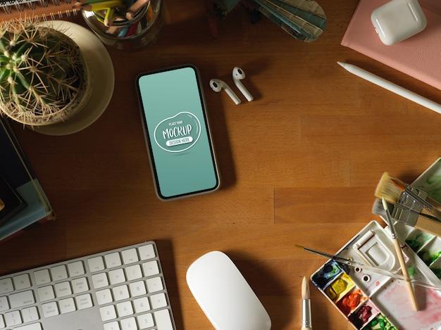 Widok Z Góry Na Drewniany Stół Z Makietą Smartfona, Klawiatury, Narzędzi Do Malowania I Materiałów Eksploatacyjnych Premium Psd