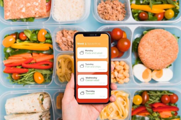 Widok Z Góry Ręki Trzymającej Smartfona Z Zaplanowanymi Posiłkami Darmowe Psd