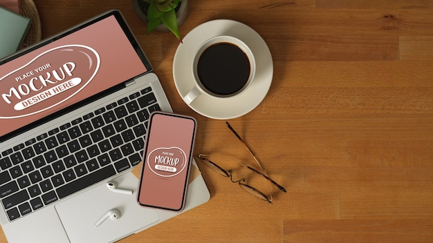 Widok Z Góry Stołu Roboczego Z Makietą Laptopa, Smartfona, Okularów, Filiżanki Kawy I Miejsca Na Kopię Premium Psd