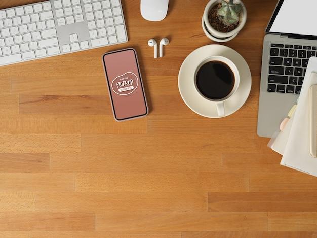Widok Z Góry Stołu Roboczego Z Makietą Smartfona, Laptopa, Urządzenia Komputerowego, Materiałów Eksploatacyjnych I Miejsca Na Kopię Premium Psd