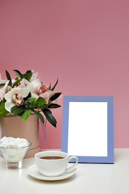 Widok Z Przodu Pusta Makieta Ramki Na Różowym Stole. Kwiaty Orchidei, Filiżanka Herbaty I Słodycze. Premium Psd