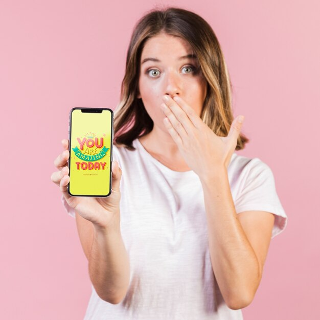 Zaskoczony, młoda kobieta, zasłaniając usta i trzymając makieta telefonu komórkowego Darmowe Psd