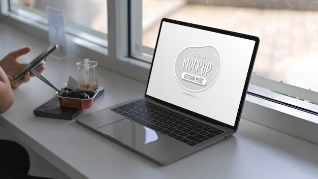 Zbliżenie Kobiety Trzymającej Smartfon Z Makiety Laptopa Na Białym Stole Premium Psd