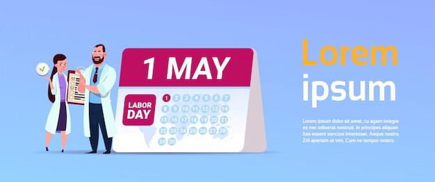 1 maja międzynarodowy święto święta pracy z lekarzem stojącym nad kalendarzem Premium Wektorów