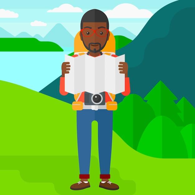 Backpacker patrząc na mapę. Premium Wektorów