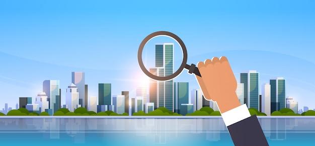 Biznesmen Ręka Trzyma Szkło Powiększające Na Duży Nowoczesny Budynek Miasta Premium Wektorów