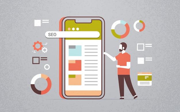 Biznesmen za pomocą wyszukiwarki seo aplikacji mobilnych Premium Wektorów