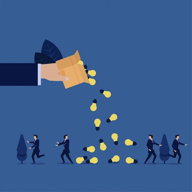 Biznesowa ręka wylewa pudełko i pomysły spadają na zespół biznesmenów. Premium Wektorów