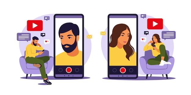 Blogerzy Wideo Kobiety I Mężczyzny Siedzą Na Kanapie Z Telefonem I Nagrywają Wideo Za Pomocą Smartfona. Różne Media Społecznościowe. Ilustracja W Stylu Płaski. Premium Wektorów