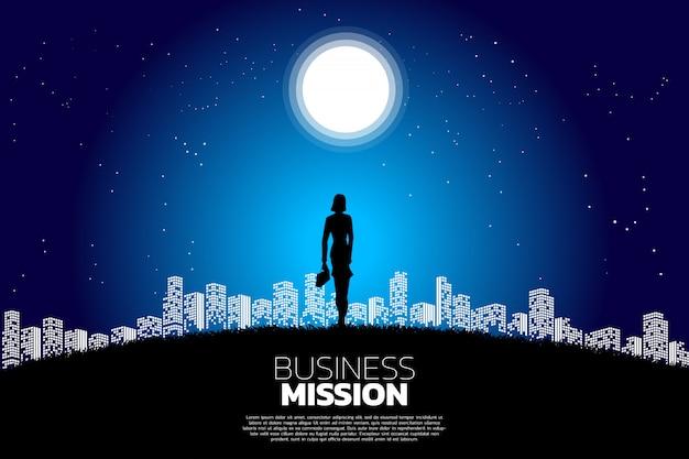 Businesswoman stojąc na księżycu w świetle miasta. Premium Wektorów